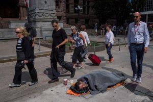 Toronto old homeless man sleeping on sidewalk